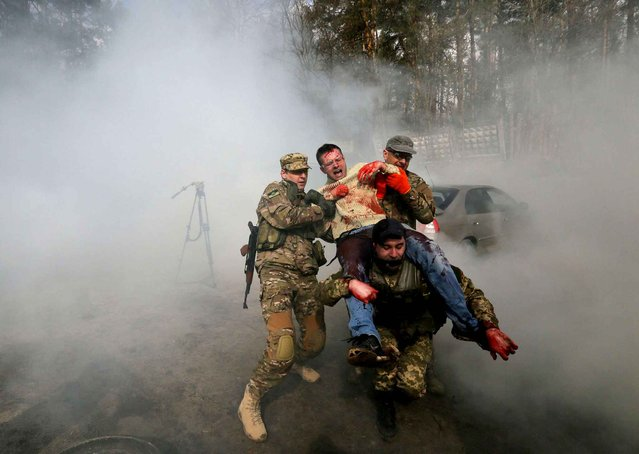Instructors conduct first aid training during an exercise by tactical medicine for heads of Kiev districts and their deputies in Kiev, Ukraine, Tuesday, March. 31, 2015. (Photo by Sergei Chuzavkov/AP Photo)