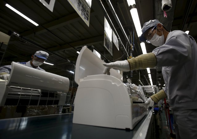 An employee of Daikin Industries Ltd inspects indoor air conditioning units at the production line at the company's Kusatsu factory in Shiga prefecture, western Japan March 20, 2015. (Photo by Yuya Shino/Reuters)