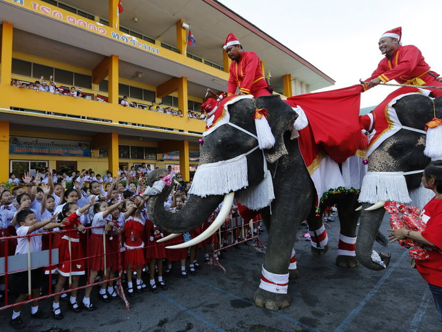 Thai elephants and mahouts, all dressed as Santa Claus, entertain students during Christmas celebrations at a school in the world heritage city of Ayutthaya, north of Bangkok, Thailand, 24 December 2018. The annual event is held every year for to celebrate the upcoming Christmas festive season and promote tourism in Ayutthaya. (Photo by Narong Sangnak/EPA/EFE)