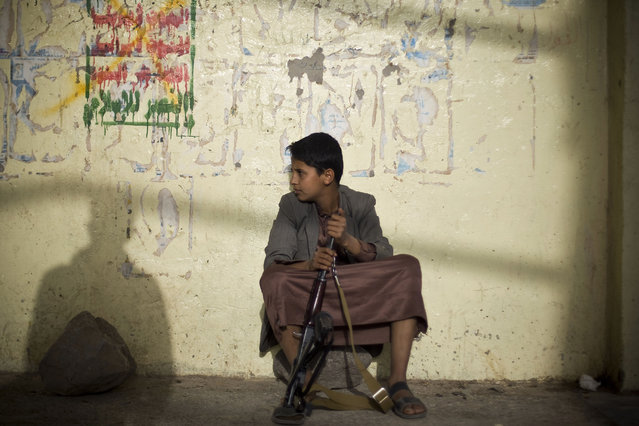 A boy holds his weapon, as he sits on guard near the site of a protest against Saudi-led airstrikes in Sanaa, Yemen, Friday, April 10, 2015. Pakistani lawmakers on Friday unanimously voted to stay out of the Saudi-led air coalition targeting Shiite rebels in Yemen in a blow to the alliance, while planes loaded with badly needed medical aid landed in Yemen's embattled capital, Sanaa, in the first such deliveries since the airstrikes started more than two weeks ago. (Photo by Hani Mohammed/AP Photo)