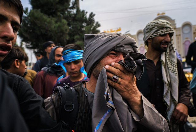 A man cries as he watches fellow Afghans get wounded after Taliban fighters use guns fire, whips, sticks and sharp objects to maintain crowd control over thousands of Afghans who continue to wait outside the Kabul Airport for a way out, on airport road in Kabul, Afghanistan, Tuesday, August 17, 2021. At least half dozen were wounded, within the hour of violent escalation, including a woman and her child. (Photo by Marcus Yam/Los Angeles Times/Rex Features/Shutterstock)