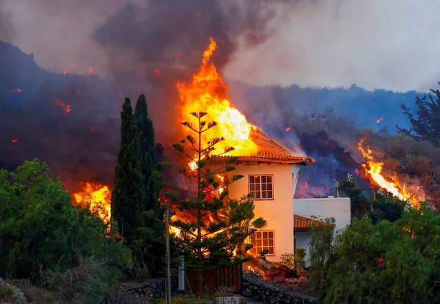 A house burns due to lava from the eruption of a volcano in the Cumbre Vieja national park at Los Llanos de Aridane, on the Canary Island of La Palma, September 20, 2021. Lava flowing from the Canary Islands' first volcanic eruption in 50 years has forced the evacuation of 5,500 people and destroyed at least 100 houses, authorities said. (Photo by Borja Suarez/Reuters)