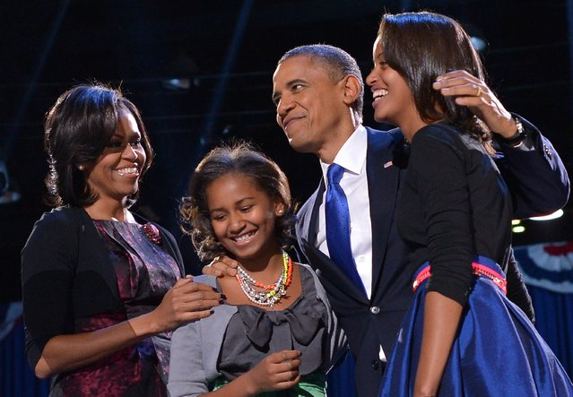 US President Barack Obama accompanied by (from L-R ) First Lady Michelle and daughters Sasha and Malia appears on stage on election night November 6, 2012 in Chicago, Illinois. (Photo by Jewel Samad/AFP Photo)