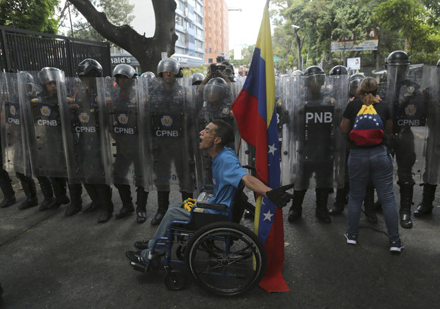 A demonstrator in a wheelchair rants at members of the Venezuelan National Police officers who temporarily blocked members of the opposition from getting to a rally against the government of President Nicolas Maduro in Caracas, Venezuela, Saturday, March 9, 2019. (Photo by Fernando Llano/AP Photo)