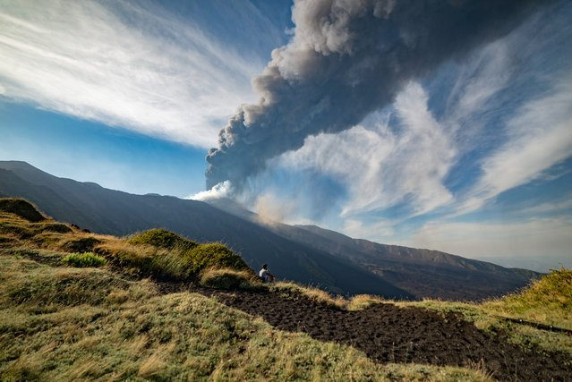 A hiker admires the view as Mt. Etna, Europe's largest active volcano, erupts in the background, in the Bove Valley of Etna Park, on the eastern slope of Mt. Etna, in Sicily, southern Italy, Sunday, July 4, 2021. Since Feb. 16, 2021, Mt. Etna has begun a series of eruptive episodes. (Photo by Salvatore Allegra/AP Photo)