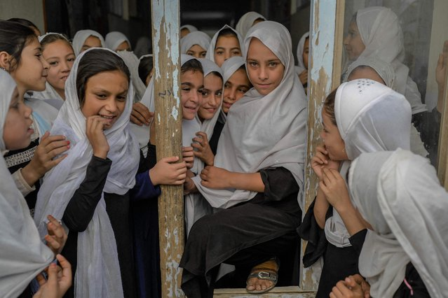 Afghan girls are pictured as they step out of their respective classes, in a school in Kandahar on September 26, 2021. (Photo by Bulent Kilic/AFP Photo)