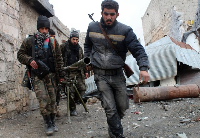 Opposition fighters carry a rocket launcher during clashes against government forces in the Sheikh Lutfi area, west of the airport in the northern Syrian city of Aleppo on January 27, 2014. Fighting inside Syria has continued unabated as opposition and regime representatives meeting in Geneva discussed ways for aid to reach besieged rebel-held areas, especially in the central city of Homs. (Photo by Salah Al-Ashkar/AFP Photo)