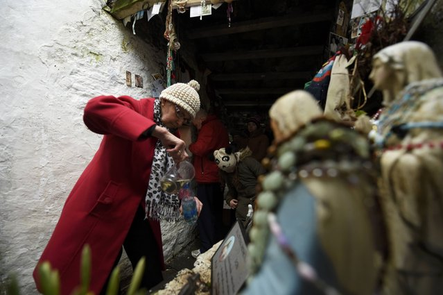A woman fills a bottle with water from the holy well of St. Brigid on a Pattern Day pilgrimage to St. Brigid in Liscannor, Ireland February 1, 2017. (Photo by Clodagh Kilcoyne/Reuters)