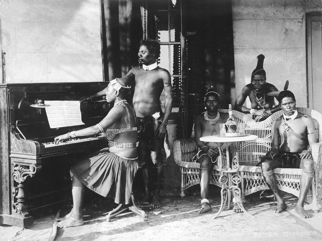 circa 1925:  A Zulu woman playing the piano while a group of others sit and listen.  (Photo by General Photographic Agency/Getty Images)