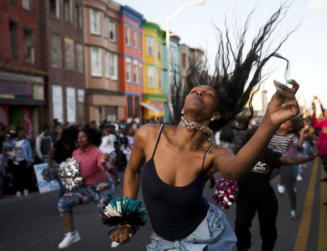 People dance Tuesday, April 28, 2015, in Baltimore. Maryland's governor vowed there would be no repeat of the looting, arson and vandalism that erupted Monday in some of the city's poorest neighborhoods. (Photo by Matt Rourke/AP Photo)