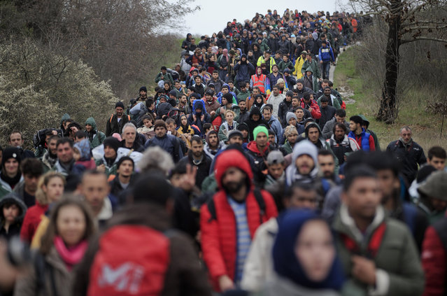 Migrants march on a road, north of Idomeni, Greece, during an attempt to reach Macedonia on a route that would bypass the border fence, Monday, March 14, 2016. Hundreds of migrants and refugees walked out of an overcrowded camp on the Greek-Macedonian border Monday, determined to use a dangerous crossing to head north. (Photo by Vadim Ghirda/AP Photo)