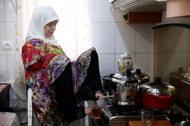 In this picture taken on Thursday, January 28, 2015, Zohreh Etezadossaltaneh uses her feet to pour tea at her home, in Tehran, Iran. Etezadossaltaneh was born without arms. (Photo by Ebrahim Noroozi/AP Photo)