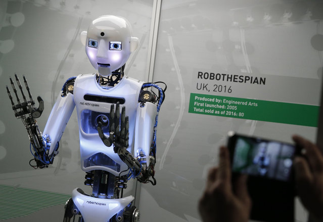 A member of the media takes a smart phone picture of RpboThespian a British built life size robot, during a press preview for the Robots exhibition held at the Science Museum in London, Tuesday, February 7, 2017. (Photo by Alastair Grant/AP Photo)