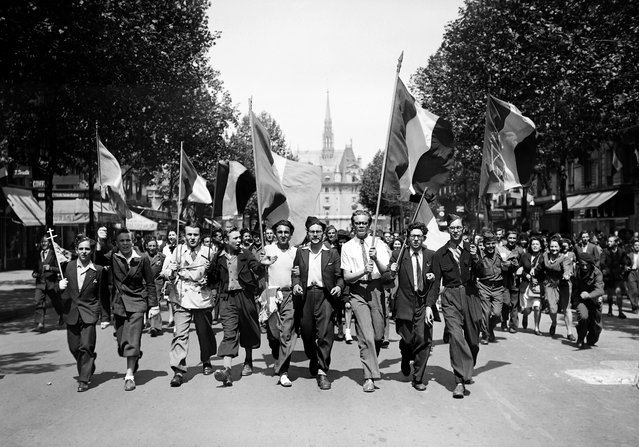 Picture dated of May 8, 1945 showing Parisians wearing French flags and marching in the streets of Paris to celebrate the unconditionnal German capitulation at the end of the second World War. (Photo by AFP/Getty Images)