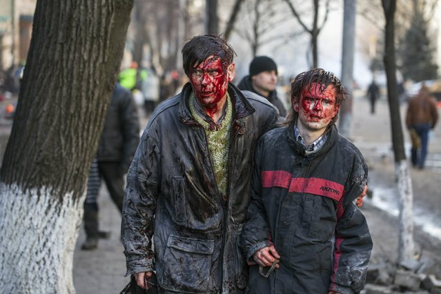 Wounded people walk after clashes with riot police in central Kiev February 18, 2014. Ukrainian riot police advanced on the heart of 12-week-old protests against President Viktor Yanukovich on Tuesday and security forces set a deadline to end disturbances after at least five protesters were reported killed in a day of clashes. (Photo by Vlad Sode/Reuters)