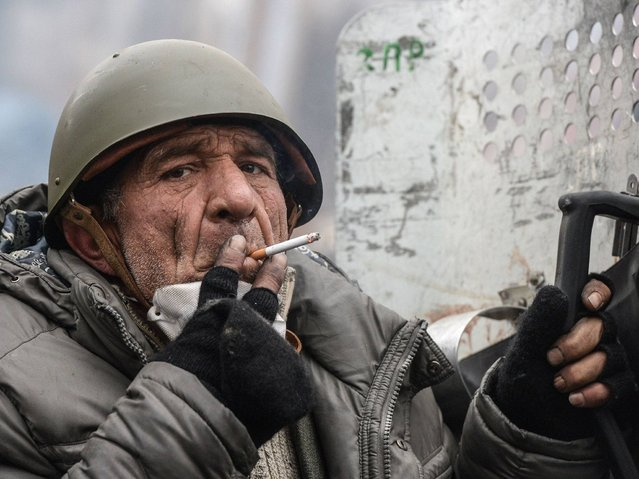 An elderly protester smokes during a break in clashes with police in central Kiev , on February 20, 2014. (Photo by Dmitry Serebryakov/AFP Photo)