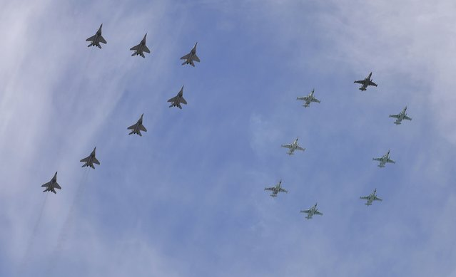 Mikoyan-Gurevich MiG-29 Fulcrum fighters and Sukhoi Su-25SM Frogfoot ground-attack planes form a number 70 as they fly over the Red Square during the Victory Day parade in Moscow, Russia, May 9, 2015. (Photo by Reuters/Host Photo Agency/RIA Novosti)