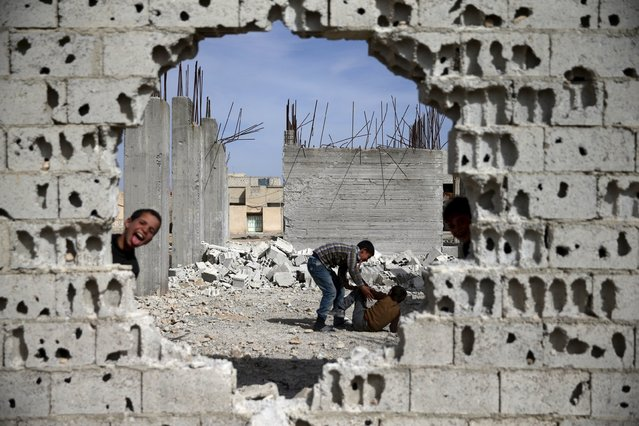 Boys play near rubble of damaged buildings in the rebel held besieged town of Douma, eastern Damascus suburb of Ghouta, Syria March 19, 2016. (Photo by Bassam Khabieh/Reuters)