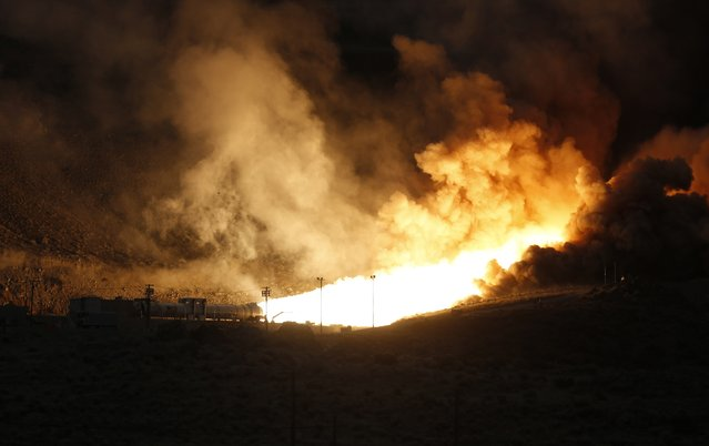 The SLS five-segment Solid Rocket Motor undergoes a static test fire at the Orbital ATK facility in Promontory, Utah March 11, 2015. The beefed-up space shuttle solid rocket motor passed a two-minute test firing in Utah on Wednesday, a key milestone toward the debut flight of NASA's deep-space launcher in 2018, the U.S. space agency said. (Photo by Jim Urquhart/Reuters)