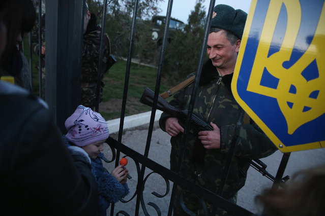 A Ukrainian soldier at the Belbek military base talks with family members, including his daughter, through the gates of the base entrance on March 3, 2014 in Lubimovka, Ukraine. (Photo by Sean Gallup/Getty Images)