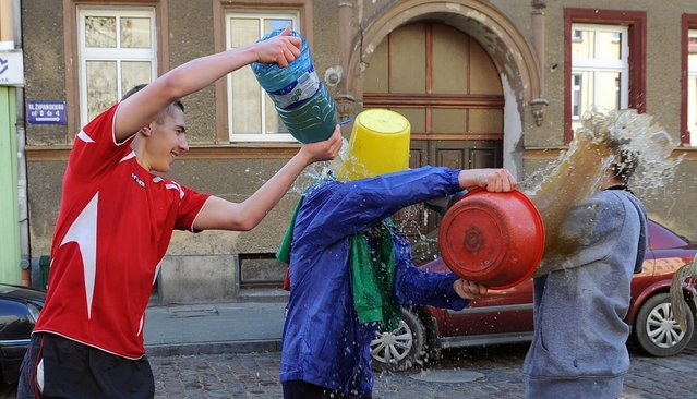 """Boys and young men soak each others with bottles and buckets of water on Easter Monday in Szczecin, Poland, 28 March 2016. In Poland the Easter Monday is often called the """"Wet Monday"""", and the tradition of splashing or even soaking each other with water is a few centuries old. (Photo by Marcin Bielecki/EPA)"""
