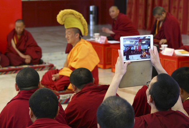 A Tibetan monk uses his tablet device to take pictures of an exam at the High-level Tibetan Buddhism College of China at Xihuang Temple in Beijing, China May 12, 2015. Monks in the college must go through exams by defending their dissertations and being interviewed by a committee made of respected monks to get an academic degree in Tibetan Buddhism, local media reported. (Photo by Reuters/Stringer)