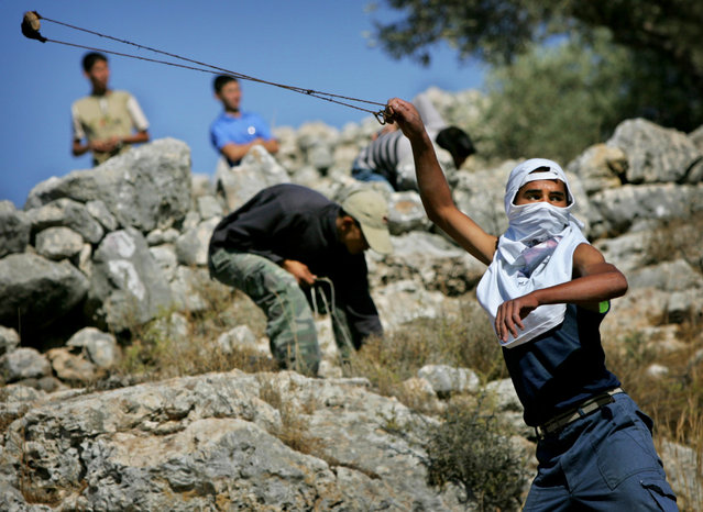 A Palestinian youth uses a sling-shot to hurl a stone at Israel soldiers during a demonstration against the construction of Israel's separation barrier in the West Bank town of Bil'in, Friday, October 21, 2005. (Photo by Oded Balilty/AP Photo)