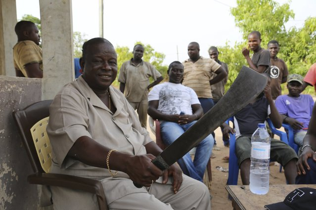 Former army chief General Antonio Indjai shows a machete used on his farm as male relatives look on outside Mansoa, Guinea-Bissau, May 8, 2015. (Photo by Emma Farge/Reuters)