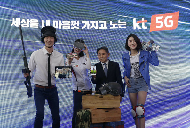 """In this Tuesday, April 2, 2019 file photo, Lee Pil-jae, second from right, Vice President at KT Corp., and models introduce various 5G services available on smarpthones during a press conference on 5G service at KT Corp's headquarters in Seoul, South Korea. South Korea's telecommunications carriers on Wednesday, April 3, have turned on super-fast 5G mobile internet networks abruptly ahead of schedule in an attempt to ensure the country becomes the first in the world to launch the services. The signs read: """"Play with the world with KT 5G"""". (Photo by Ahn Young-joon/AP Photo/File)"""