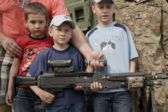 Romanian children get help from their father as they pose with a machine-gun, standing next to an U.S. serviceman in Ploiesti, Romania, Wednesday, May 13, 2015. (Photo by Vadim Ghirda/AP Photo)