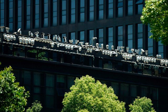 This picture shows surveillance cameras being installed on the rooftop of a office building in Hangzhou, in east China's Zhejiang province on May 29, 2019. (Photo by AFP Photo/Stringer)