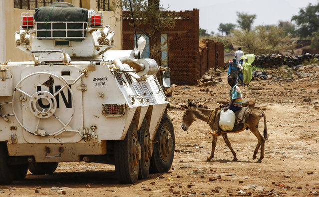 A Sudanese boy rides a donkey past a UN-African Union mission in Darfur (UNAMID) armoured vehicle in the war-torn town of Golo in the thickly forested mountainous area of Jebel Marra in central Darfur on June 19, 2017. The town was a former rebel bastion which was recently captured by Sudanese government forces. The United States' top envoy in Sudan visited Golo on June 19, 2017 on the second day of his four-day trip to Darfur to assess security in the war-torn region as the UN prepares to downsize its 17,000-strong peacekeeping force. His visit also comes just weeks before President Donald Trump's administration decides whether to permanently lift a two-decades old US trade embargo on Sudan. (Photo by Ashraf Shazly/AFP Photo)