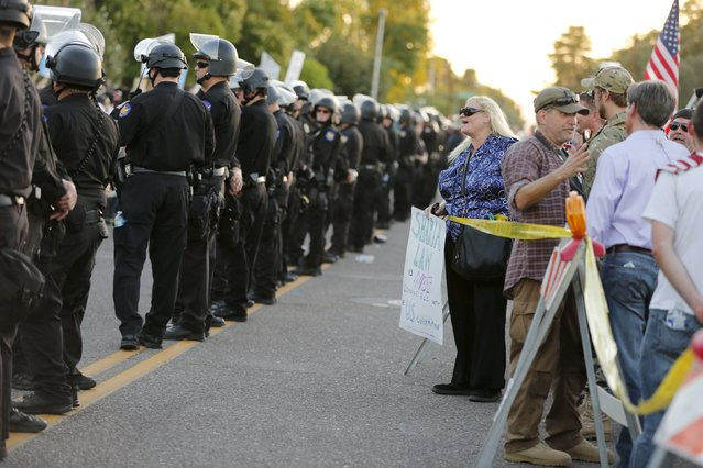 """A police line separates people attending the """"Freedom of Speech Rally Round II"""" from counter demonstrators outside the Islamic Community Center in Phoenix, Arizona May 29, 2015.  More than 200 protesters, some armed, berated Islam and its Prophet Mohammed outside an Arizona mosque on Friday in a provocative protest that was denounced by counterprotesters shouting """"Go home, Nazis,"""" weeks after an anti-Muslim event in Texas came under attack by two gunmen.  REUTERS/Nancy Wiechec"""