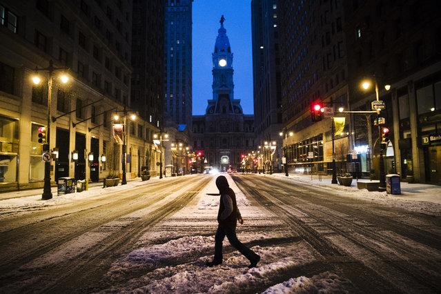 A man crosses South Broad Street in view of City Hall during a winter storm in Philadelphia, Tuesday, March 14, 2017. (Photo by Matt Rourke/AP Photo)