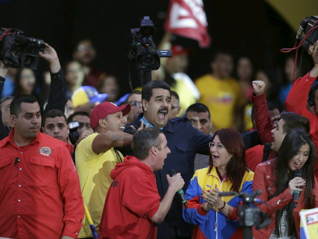 Venezuela's President Nicolas Maduro (C) reacts during the final campaign rally of Venezuela's United Socialist Party (PSUV) in Caracas, June 26, 2015. Members of Venezuela's United Socialist Party (PSUV) will participate in nationwide voting on Sunday, June 28, to elect their candidates for the 2015 parliamentary elections which will be held on December 6, 2015, according to local media. (Photo by Jorge Dan Lopez/Reuters)