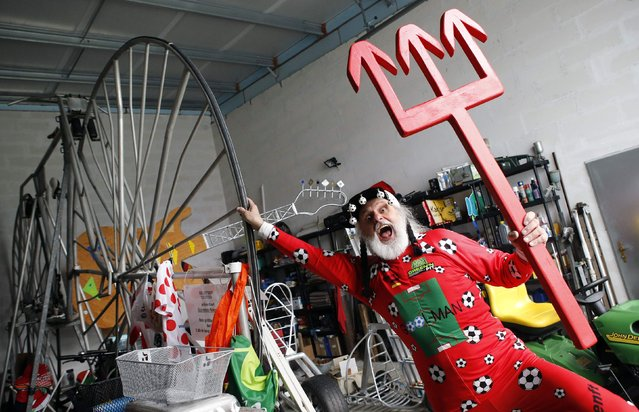 """German bicycle designer Didi Senft, also known as """"El Diablo"""", poses with his trident after presenting his new bicycle creation to commemorate the 2014 FIFA World Cup, in the town of Storkow, southeast of Berlin April 18, 2014. Senft, who has had an entry in the Guiness Book of Records for the world's largest bicycle, worked some 100 hours on this bicycle, he said. (Photo by Fabrizio Bensch/Reuters)"""