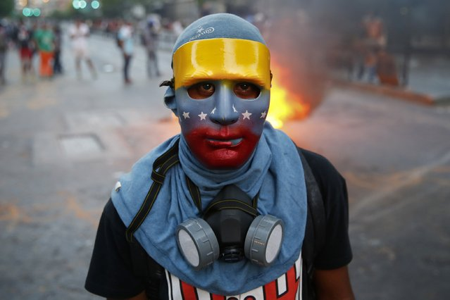 "An anti-government protester, wearing a mask in the colors of the Venezuelan flag, stands at a barricade during riots in Caracas, the nation's capital, on April 20, 2014. Masked youths battled police, protesters burned and hung effigies of President Nicolas Maduro from lampposts as marchers demanded the ""resurrection"" of democracy on a volatile Easter Sunday in Venezuela. (Photo by Jorge Silva/Reuters)"