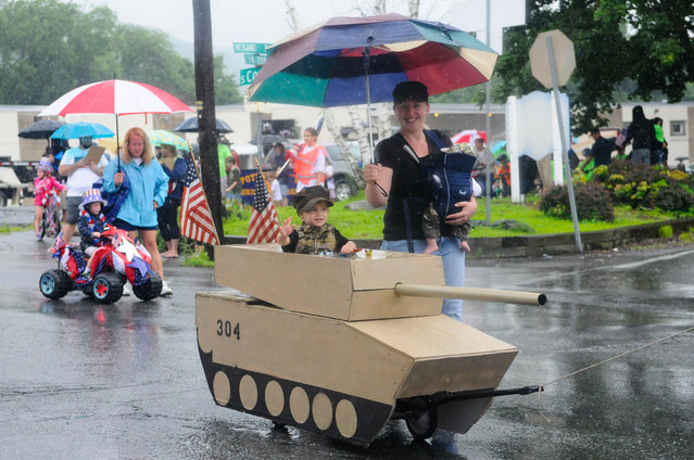"""Patrick Murphy, Port Carbon, Pa., rides in a tank pulled by his father Bill Murphy as his mother Cassandra Murphy carries Keegan Murphy as they make their way down S. Coal Street during the annual Fourth of July Parade nicknamed the """"Baby Parade"""" in Port Carbon, Pa., on Saturday, July 4, 2015. The event was hosted by The Port Carbon Citizens Committee. (Photo by Jacqueline Dormer/The Republican-Herald via AP Photo)"""