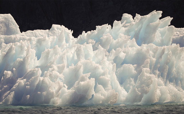 A large iceberg melts into jagged edges as it floats in Eriks Fjord near the town of Narsarsuaq in southern Greenland July 26, 2009. (Photo by Bob Strong/Reuters)