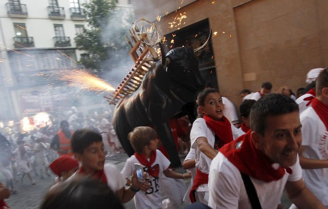 "Revellers run from the ""Fire Bull"", a man carrying a metal structure shaped like a bull and loaded with fireworks, on the second day of the San Fermin festival in Pamplona, northern Spain, July 7, 2015. Visitors to the nine-day festival, depicted in Ernest Hemingway's 1926 novel ""The Sun Also Rises"", take part in activities including The Running Of The Bulls, an early morning half mile dash from the corral to the bullring alongside six bulls destined to die in the afternoon's corrida. (Photo by Joseba Etxaburu/Reuters)"