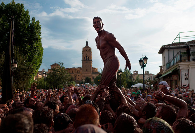 """A man covered in black grease shouts above the crowd during the traditional festivities of the Cascamorras, in Guadix, near Granada, on September 9, 2019. Every September 6, a villager from Guadix, performing the """"Cascamorras"""" oddball character, walks three kilometres to the village of Baza to stage an attempt to recapture a statue of the Pieta virgin before returning to Guadix, after three days, where he will be punished by locals for his failure. (Photo by Jorge Guerrero/AFP Photo)"""