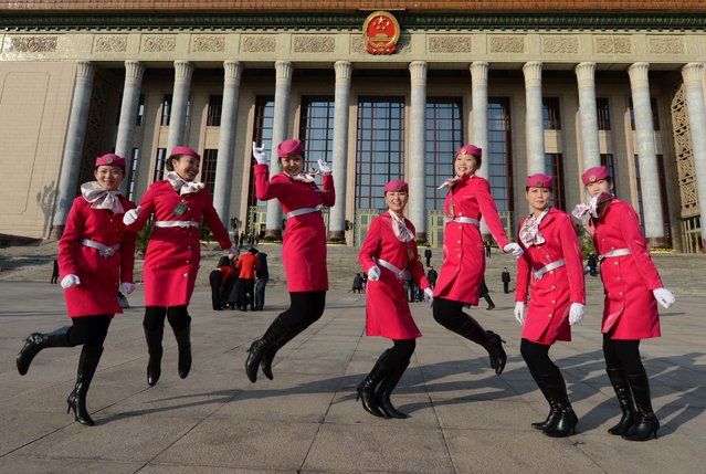 Chinese hostesses jump before the opening session of the Chinese Communist Party's five-yearly Congress at the Great Hall of the People in Beijing on November 9, 2012. The week-long congress, held every five years, will end with a transition of power to Vice President Xi Jinping, who will govern for the coming decade amid growing pressure for reform of the communist regime's iron-clad grip on power. (Photo by Mark Ralston/AFP Photo)
