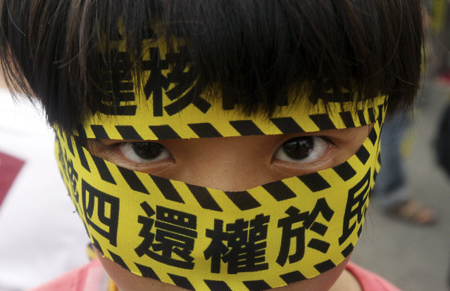 "A Taiwanese boy wears a slogan reading ""Stop the 4th Nuclear Power Plant. Give Power Back to People"", during a protest against the construction of Taiwan's fourth nuclear power plant to be completed in Taipei, Taiwan, Sunday, April 27, 2014. Taiwan's opposition party has long opposed nuclear power and public caution over nuclear safety has risen following the 2011 nuclear disaster in Japan. (Photo by Chiang Ying-ying/AP Photo)"