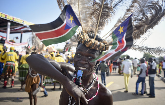 A South Sudanese man wears a headdress of feathers and the national flag, as he attends an independence day ceremony in the capital Juba, South Sudan, Thursday, July 9, 2015. (Photo by Jason Patinkin/AP Photo)