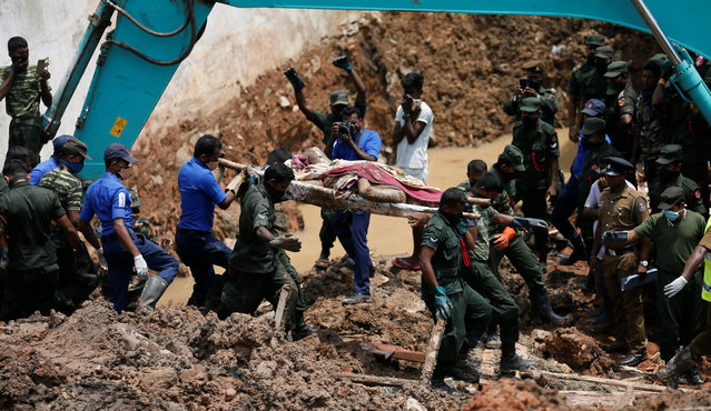Members of the military carry a dead victim during a rescue mission after a garbage dump collapsed and buried dozens of houses in Colombo, Sri Lanka April 16, 2017. (Photo by Dinuka Liyanawatte/Reuters)