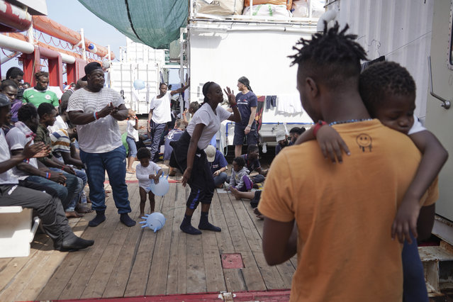 Rescued migrants dance and sing on the deck of the Ocean Viking as it sails in the Mediterranean Sea, Saturday, September 21, 2019. The humanitarian ship operated by SOS Mediterranee and Doctors Without Borders is still waiting to be assigned a place of safety to disembark 182 people rescued after fleeing Libya. (Photo by Renata Brito/AP Photo)