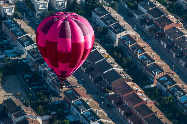 A hot air balloon flies over Igualada during an early flight as part of the European Balloon Festival on July 10, 2015 in Igualada, Spain. Now is the 19th year of the European Balloon Festival, the most important hot air Balloon event in Spain and one of the biggest in Europe. (Photo by David Ramos/Getty Images)
