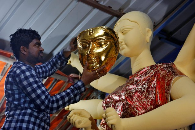 An artisan tries a gold face on an idol of the Hindu goddess Durga during a media preview inside a workshop during preparations for the upcoming Durga Puja festival in Kolkata, India, September 26, 2019. (Photo by Rupak De Chowdhuri/Reuters)