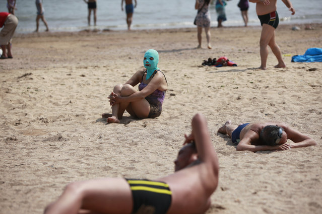 A woman, wearing a nylon mask, sits on the shore during her visit to a beach in Qingdao, Shandong province July 6, 2012. (Photo by Aly Song/Reuters)