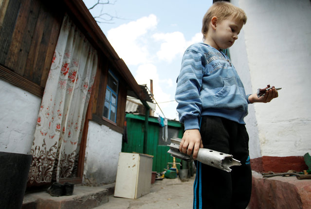 A boy holds the remains of a mortar shell which hit a residential building in the village of Staromikhailovka, outside the separatist-held city of Donetsk, Ukraine, May 24, 2016. (Photo by Alexander Ermochenko/Reuters)